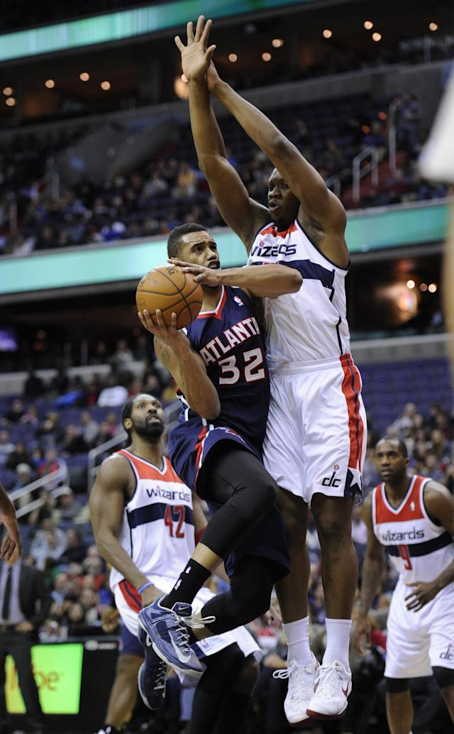 Atlanta Hawks forward Mike Scott (32) goes to the basket against Washington Wizards center Kevin Seraphin, right, of France, during the first half of an NBA basketball game, Saturday, Nov. 30, 2013, in Washington. Seraphin was called for a foul on the play. Also seen are Washington Wizards power forward Nene (42) and Martell Webster (9). (AP Photo/Nick Wass)