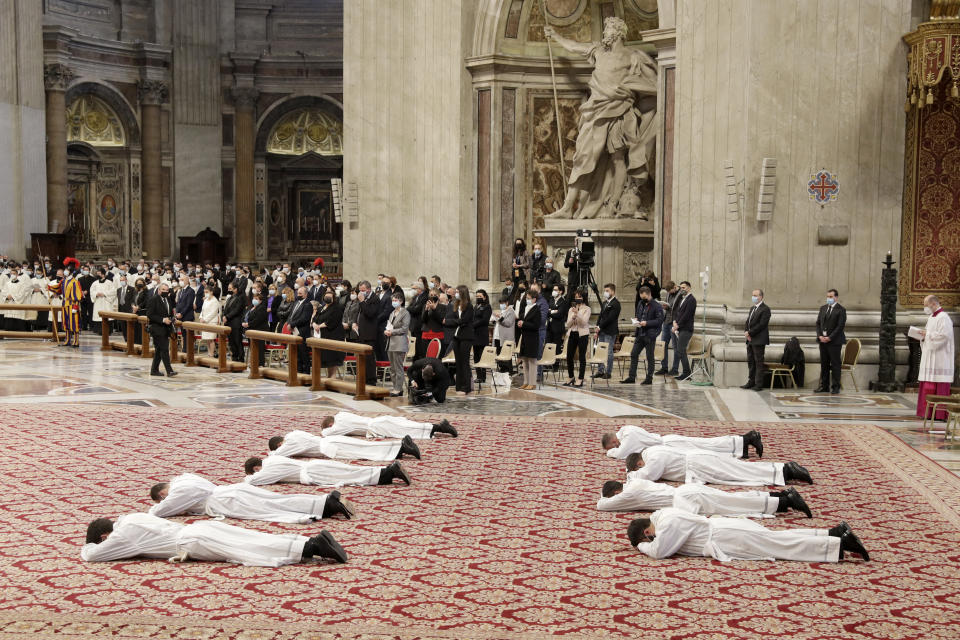 Nine new priests lie face down on the ground during their ordination ceremony lead by Pope Francis, inside St. Peter's Basilica, at the Vatican, Sunday, April 25, 2021. (AP Photo/Andrew Medichini)