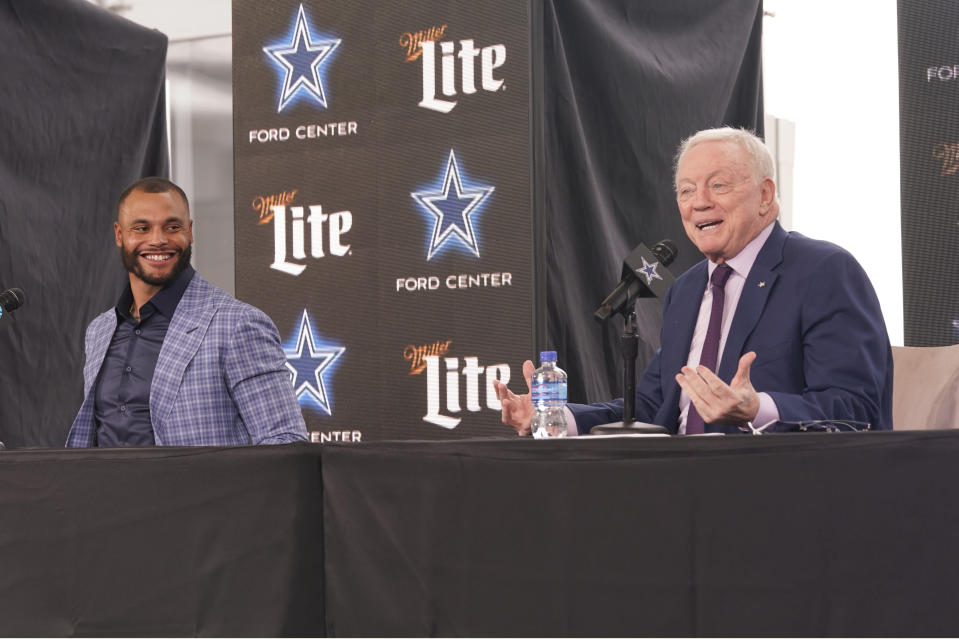 Dallas Cowboys quarterback Dak Prescott, left, looks on and smiles as team owner Jerry Jones speaks during a news conference at the team's NFL football practice facility in Frisco, Texas, Wednesday, March 10, 2021. The Cowboys and Prescott have finally agreed on the richest contract in club history, two years after negotiations began with the star quarterback. (AP Photo/LM Otero)