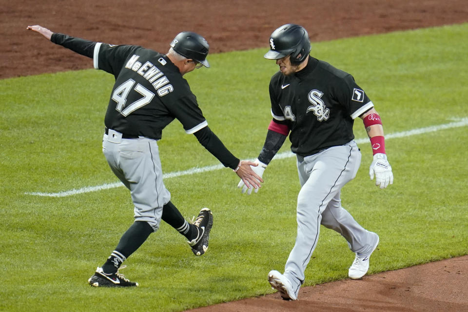 Chicago White Sox's Yasmani Grandal (24) celebrates with third base coach Joe McEwing as he rounds third base after hitting a three-run home run off Pittsburgh Pirates starting pitcher Tyler Anderson during the seventh inning of a baseball game in Pittsburgh, Tuesday, June 22, 2021. (AP Photo/Gene J. Puskar)