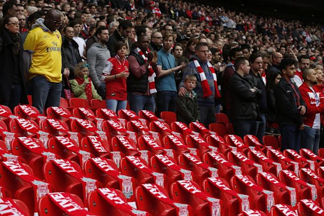 Supporters observe a minute silence around 96 empty seats covers with Liverpool scarves in memory of the victims of Hillsborough before the start of the English FA Cup semifinal soccer match between Wigan Athletic and Arsenal at Wembley Stadium in London, Saturday, April 12, 2014. 96 soccer supporters died and many were injured at the Hillsborough Stadium in Sheffield on April 15, 1989, during the FA Cup semifinal soccer match between Liverpool and Nottingham Forest. (AP Photo/Sang Tan)