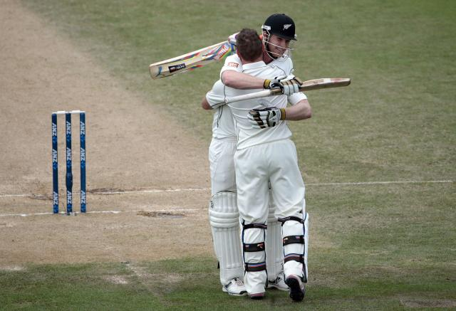 New Zealand's Brendon McCullum acknowledges his 300 with teammate James Neesham (back) against India during the second innings of play on day five of the second international test cricket match at the Basin Reserve in Wellington, February 18, 2014. McCullum made the highest score ever for a New Zealander with 302. REUTERS/Anthony Phelps (NEW ZEALAND - Tags: SPORT CRICKET)