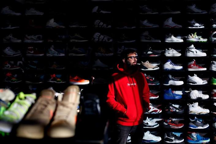 """Adeel Shams stands in front of a wall of collectible sneakers at his CoolKicks resale store in Los Angeles. Customers increasingly are converting their collections into quick cash. <span class=""""copyright"""">(Dania Maxwell / Los Angeles Times)</span>"""