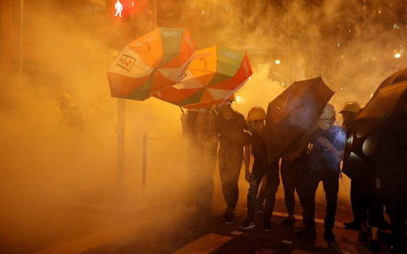 Pro-democracy protesters shield themselves with umbrellas in tear gas as they clash with police in Hong Kong - REUTERS