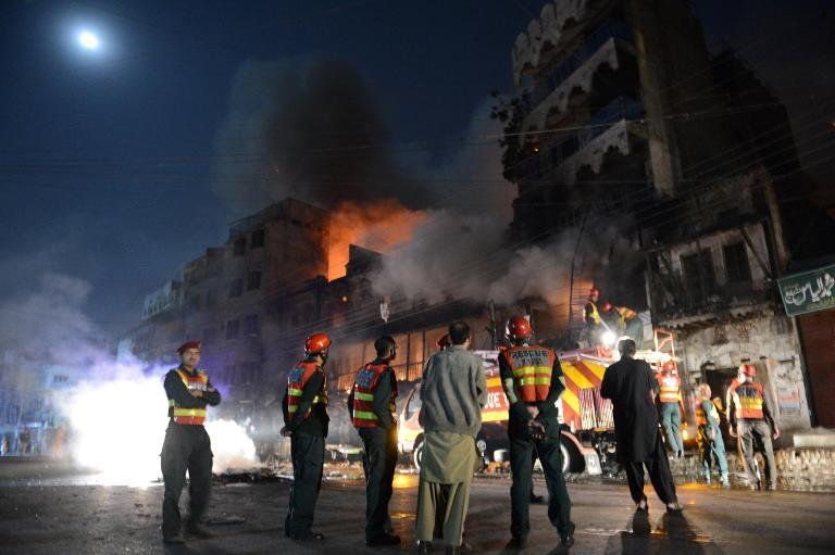 Security personnel gather outside a burning market after sectarian clashes near a Sunni mosque during the Shiite Muslim procession in Rawalpindi on November 15, 2013