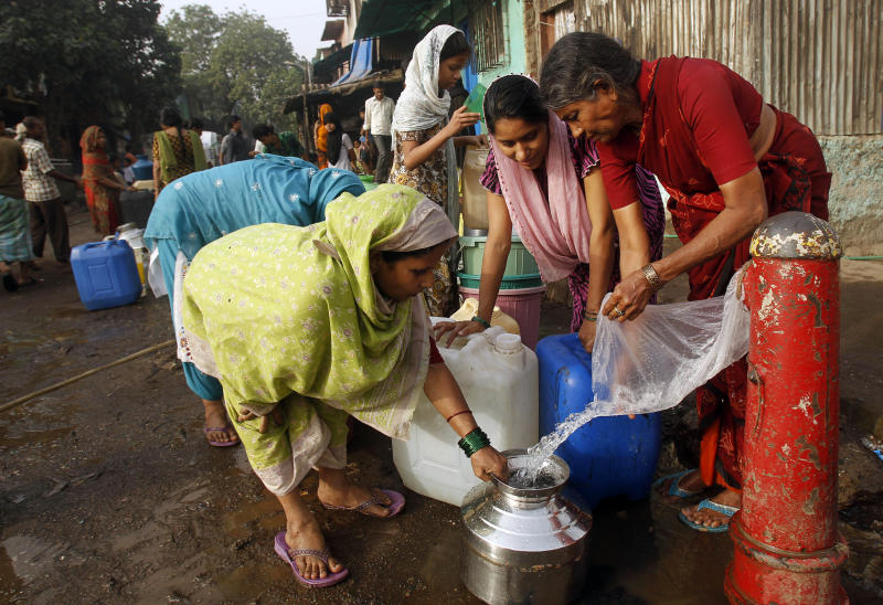 Indian women collect water from a broken pipe in a slum on the outskirts of Mumbai, India, Thursday, March 22, 2012. The U.N. estimates that more than one in six people worldwide do not have access to 20-50 liters (5-13 gallons) of safe freshwater a day to ensure their basic needs for drinking, cooking and cleaning. (AP Photo/Rafiq Maqbool)