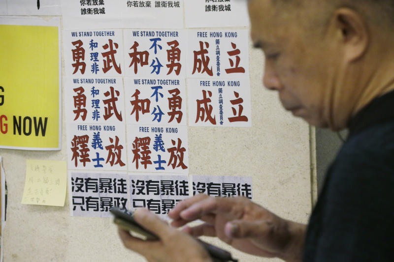 """A man walks past the posters with Chinese words read """"Peaceful protesters and frontliners stand together"""" at a shopping mall in Hong Kong, Sunday, Nov. 3, 2019. (AP Photo/Dita Alangkara)"""