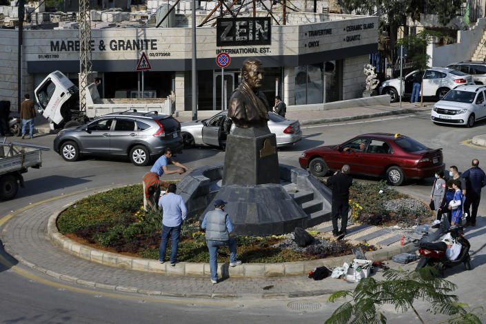 People gather near a statue of Iranian General Qassem Soleimani, who was the head of Iran's Quds force, that was installed to commemorate the anniversary of his killing, in a U.S. drone strike in Baghdad, in Ghobeiry, a southern suburb of Beirut, Lebanon, Wednesday, Jan. 6, 2021. (AP Photo/Bilal Hussein)