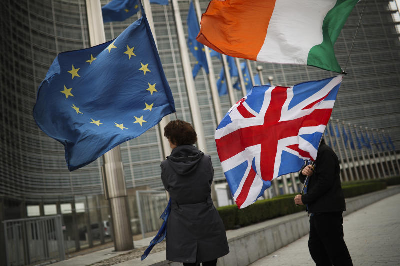 Two anti Brexit people hold EU, Ireland and Union Flags as they wait for the departure of UK Brexit secretary Stephen Barclay during his meeting with European Union chief Brexit negotiator Michel Barnier at the European Commission headquarters in Brussels, Friday, Oct. 11, 2019. The European Union said Friday that talks with the United Kingdom to find an amicable divorce with the United Kingdom are back on track, despite huge challenges and a tight end-of-month deadlime looming large. (AP Photo/Francisco Seco)