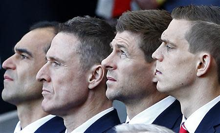 Liverpool's captain Steven Gerrard (2nd R) and Everton Manager Roberto Matinez (L) react during a memorial service to mark the 25th anniversary of the Hillsborough disaster at Anfield in Liverpool, northern England April 15, 2014. REUTERS/Darren Staples