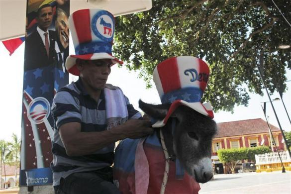 A friend of Colombian attorney Silvio Carrasquilla dresses a baby donkey Demo as the mascot of the U.S. Democratic Party in front of a poster of U.S. President Barack Obama, outside Carrasquilla's home in Turbaco, near Cartagena, April 11, 2012.