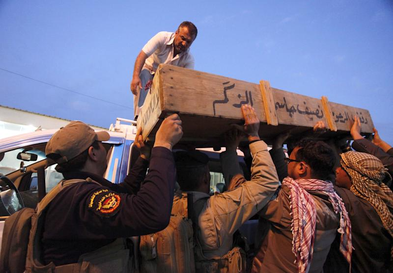Family members of Ahmed Mohammed, 34, who was killed in a car bomb attack loads his coffin onto a vehicle before burial in Najaf, 100 miles (160 kilometers) south of Baghdad, Iraq, Tuesday, March 20, 2012. Officials say attacks across Iraq have killed and wounded scores of people, police said, in a spate of violence that was dreaded in the days before Baghdad hosts the Arab world's top leaders. (AP Photo / Alaa al-Marjani)