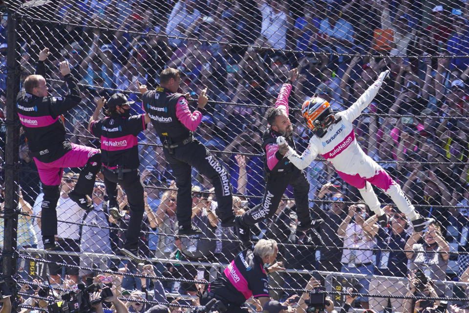 Helio Castroneves of Brazil celebrates with his team as he climbs the fence at the start/finish line after winning the Indianapolis 500 auto race at Indianapolis Motor Speedway in Indianapolis, Sunday, May 30, 2021. (AP Photo/Michael Conroy)