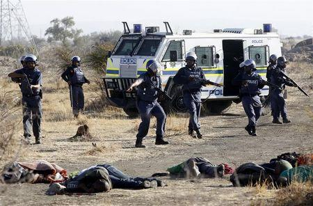 ATTENTION EDITORS - VISUAL COVERAGE OF SCENES OF DEATH AND INJURY A policeman gestures in front of some of the dead miners after they were shot outside a South African mine in Rustenburg, 100 km (62 miles) northwest of Johannesburg, August 16, 2012. South African police opened fire on Thursday against thousands of striking miners armed with machetes and sticks at Lonmin's Marikana platinum mine, leaving several bloodied corpses lying on the ground. A Reuters cameraman said he saw at least seven bodies after the shooting, which occurred when police laying out barricades of barbed wire were outflanked by some of an estimated 3,000 miners massed on a rocky outcrop near the mine, 100 km (60 miles) northwest of Johannesburg. REUTERS/Siphiwe Sibeko (SOUTH AFRICA - Tags: CIVIL UNREST CRIME LAW TPX IMAGES OF THE DAY) TEMPLATE OUT