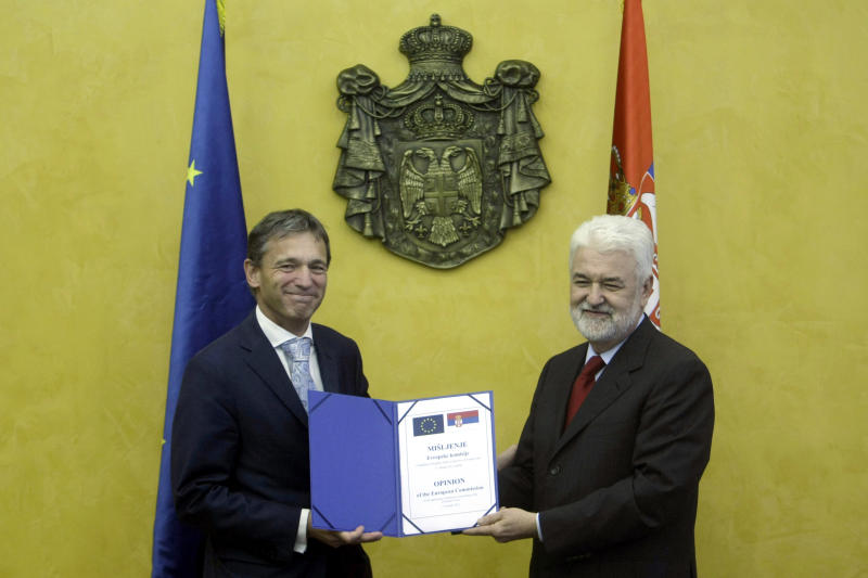 Vincent Degert, the head of the EU mission in Serbia, left, presents the formal response of the European Commission on the application of Serbia for membership of the EU to Serbian Prime Minister, Mirko Cvetkovic, in Belgrade, Serbia, Wednesday, Oct. 12, 2011. The EU's executive commision recommended on Wednesday that Serbia be granted the status of a candidate for membership in the bloc, but it said it would not set a date for formal accession talks until Serbia and Kosovo normalize their ties. (AP Photo/ Marko Drobnjakovic)