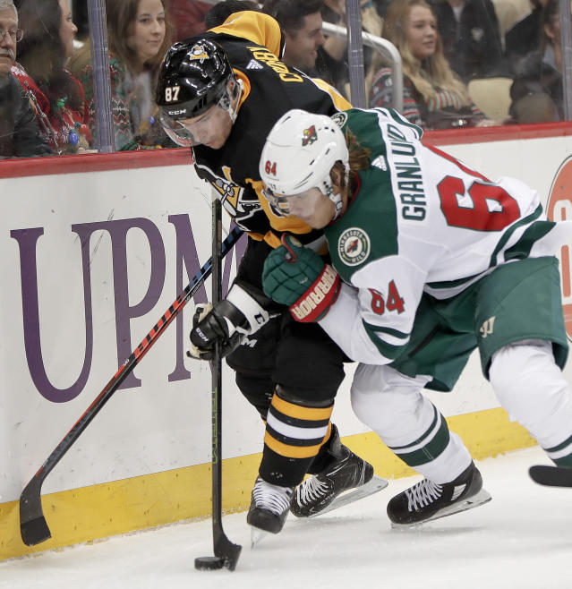 Pittsburgh Penguins' Sidney Crosby (87) and Minnesota Wild's Mikael Granlund (64) battle along the boards for the puck during the second period of an NHL hockey game Thursday, Dec. 20, 2018, in Pittsburgh. (AP Photo/Keith Srakocic)