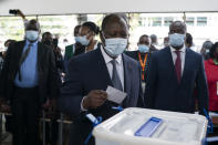 Ivory Coast President Alassane Ouattara casts his vote at a polling station during presidential elections in Abidjan, Ivory Coast, Saturday, Oct. 31, 2020. Tens of thousands of security forces are deployed across Ivory Coast on Saturday as the leading opposition parties boycotted the election, calling President Ouattara's bid for a third term illegal. (AP Photo/Leo Correa)