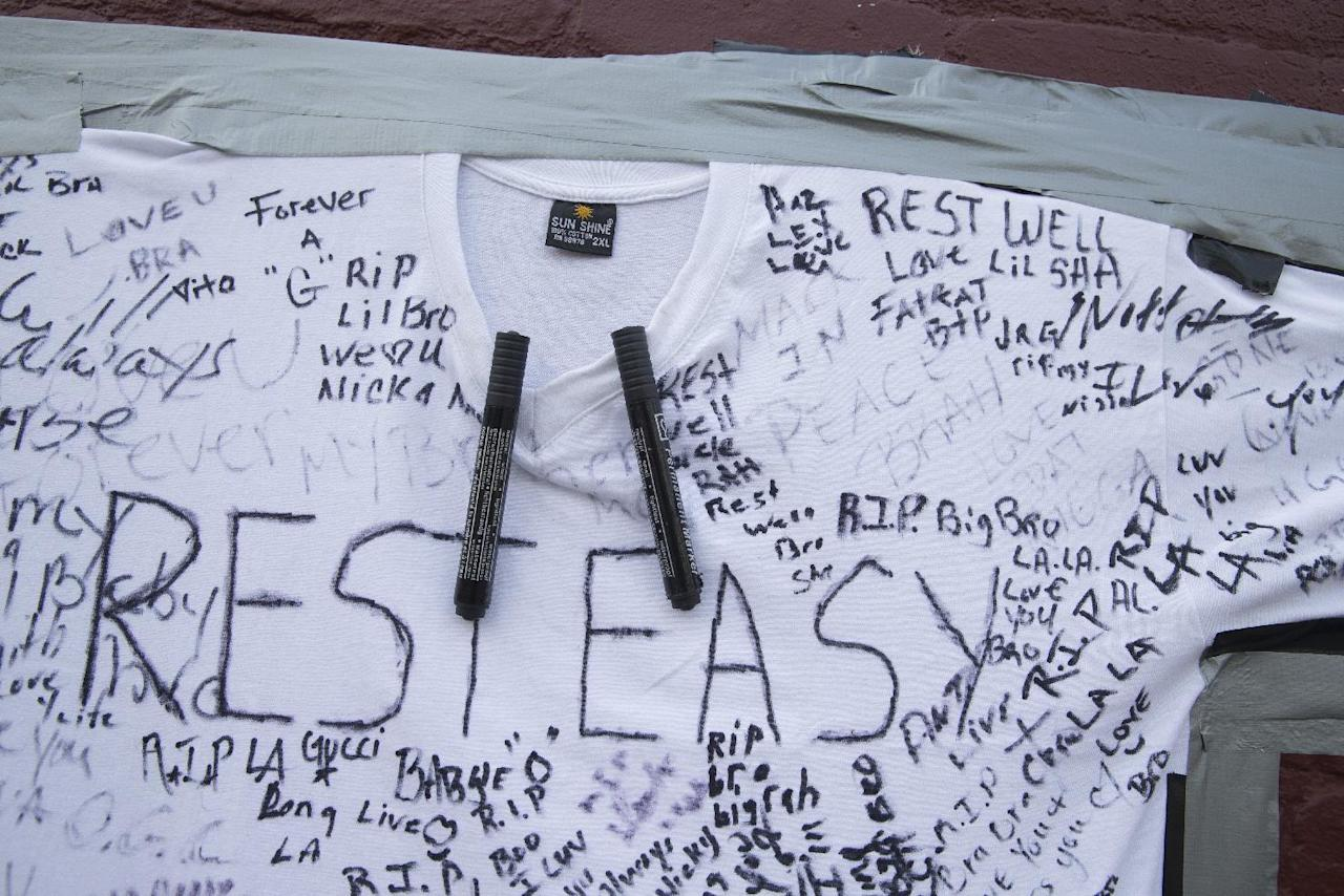 A t-shirt covered with written messages are taped on a wall at memorial to Lawrence Campbell, who allegedly shot and killed 23-year-old Jersey City police officer Melvin Santiago, Monday, July 14, 2014, in Jersey City, N.J. Campbell was also killed at the scene after police officers returned fire. (AP Photo/John Minchillo)