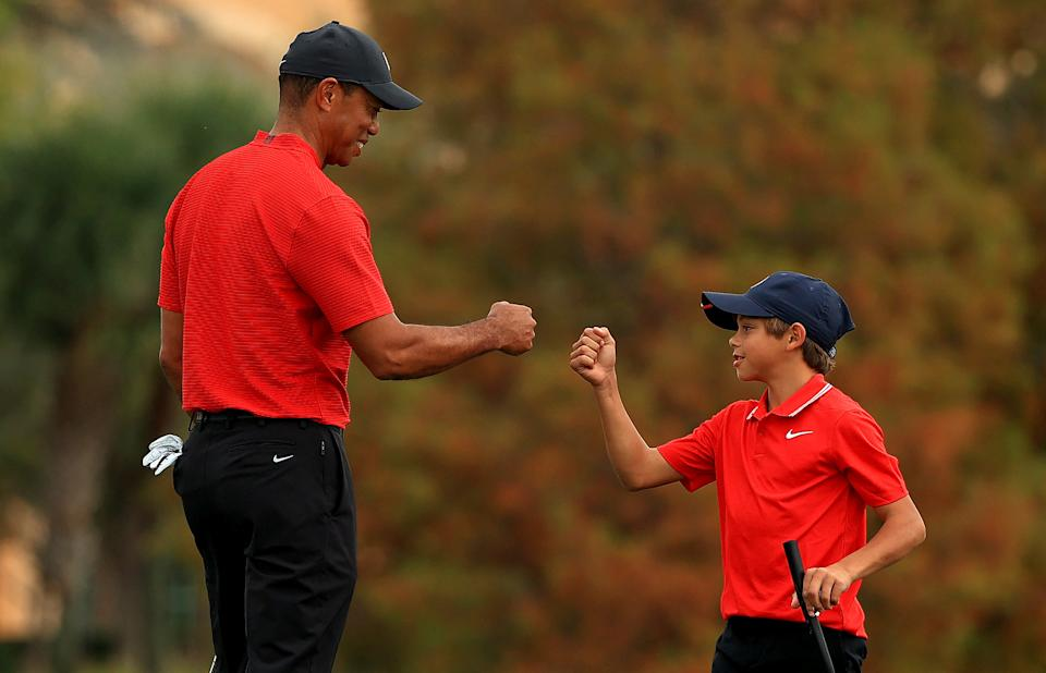 Tiger Woods of the United States and son Charlie Woods fist bump on the 18th hole during the final round of the PNC Championship at the Ritz Carlton Golf Club on December 20, 2020 in Orlando, Florida. (Photo by Mike Ehrmann/Getty Images)