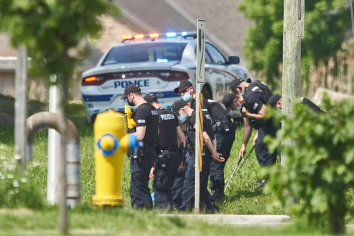 Police officers look for evidence in London, Ontario after four families were killed in a truck (Geoff Robins / The Canadian Press via AP)