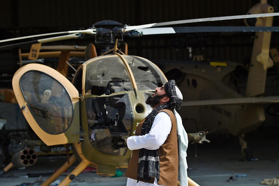 A Taliban member looks up standing next to a damaged helicopter at the airport in Kabul on August 31, 2021, after the US has pulled all its troops out of the country to end a brutal 20-year war -- one that started and ended with the hardline Islamist in power. (Photo by Wakil KOHSAR / AFP) (Photo by WAKIL KOHSAR/AFP via Getty Images)