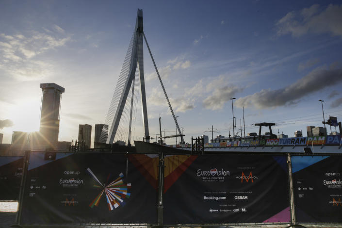 A fence blocks the view on the opening ceremony of Eurovision Song Contest as the sun sets over the iconic Erasmus bridge in the center of Rotterdam, Netherlands, Sunday, May 16, 2021. (AP Photo/Peter Dejong)