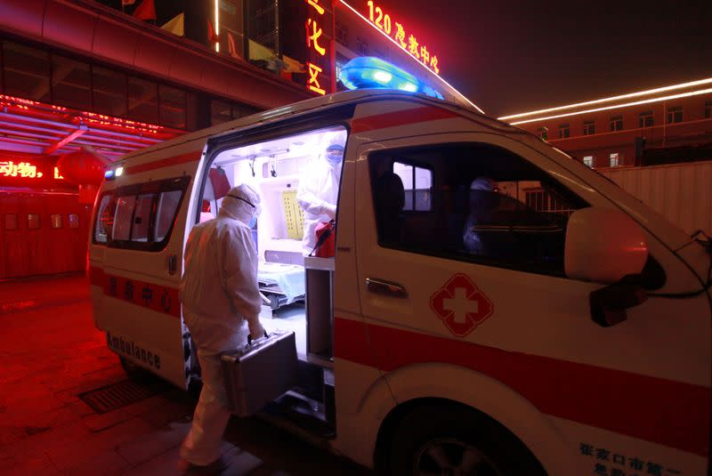 Medical worker in protective suit gets onto an ambulance at a hospital, following an outbreak of the novel coronavirus in the country, in Zhangjiakou