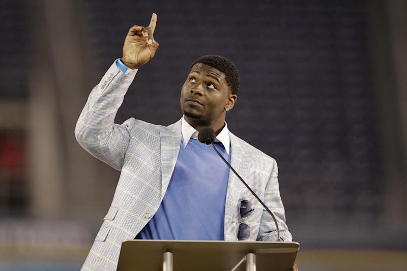 Former San Diego Chargers running back LaDainian Tomlinson points upward during a public memorial service for the late NFL football player Junior Seau at Qualcomm Stadium Friday, May 11, 2012, in San Diego. Seau committed suicide on May 2 at his Oceanside, Calif., home. He played parts of 20 seasons in the NFL, with the SanDiego Chargers, Miami Dolphins and New England Patriots. (AP Photo/ Gregory Bull)