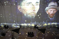 """Patrons socially distance as they look at the moving images cast on the walls, floors and reflecting mirrors during a virtual display titled """"Immersive Van Gogh"""" on Thursday, Feb. 18, 2021, at the Lighthouse ArtSpace, in Chicago. (AP Photo/Shafkat Anowar)"""