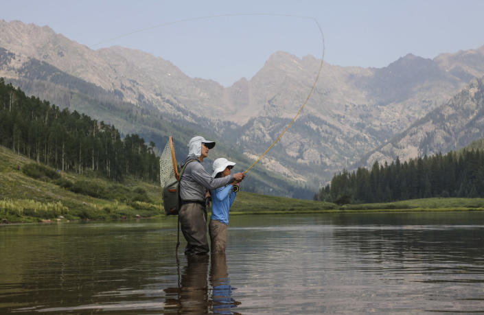 Robert Yi teaches his daughter Sylvana, 11, of Evergreen, how to fly fish, Sunday, July 25, 2021, at Piney Lake outside of Vail, Colo. The lake is a popular destination for many recreational activities. (Chris Dillmann/Vail Daily via AP)