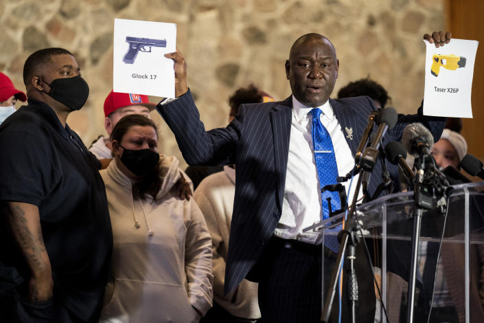 Attorney Ben Crump, representing the family of Daunte Wright, holds up images depicting X26P Taser and a Glock 17 handgun during a news conference at New Salem Missionary Baptist Church, Thursday, April 15, 2021, in Minneapolis. (AP Photo/John Minchillo)