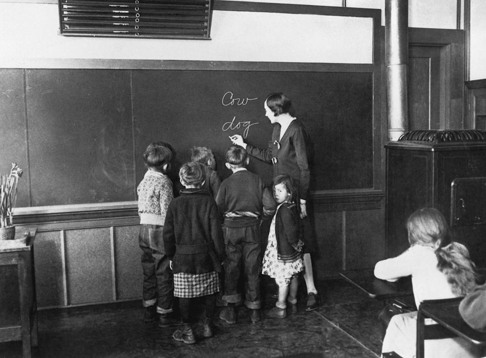 <p>Children gather around a teacher as she writes different animal names on the blackboard. </p>