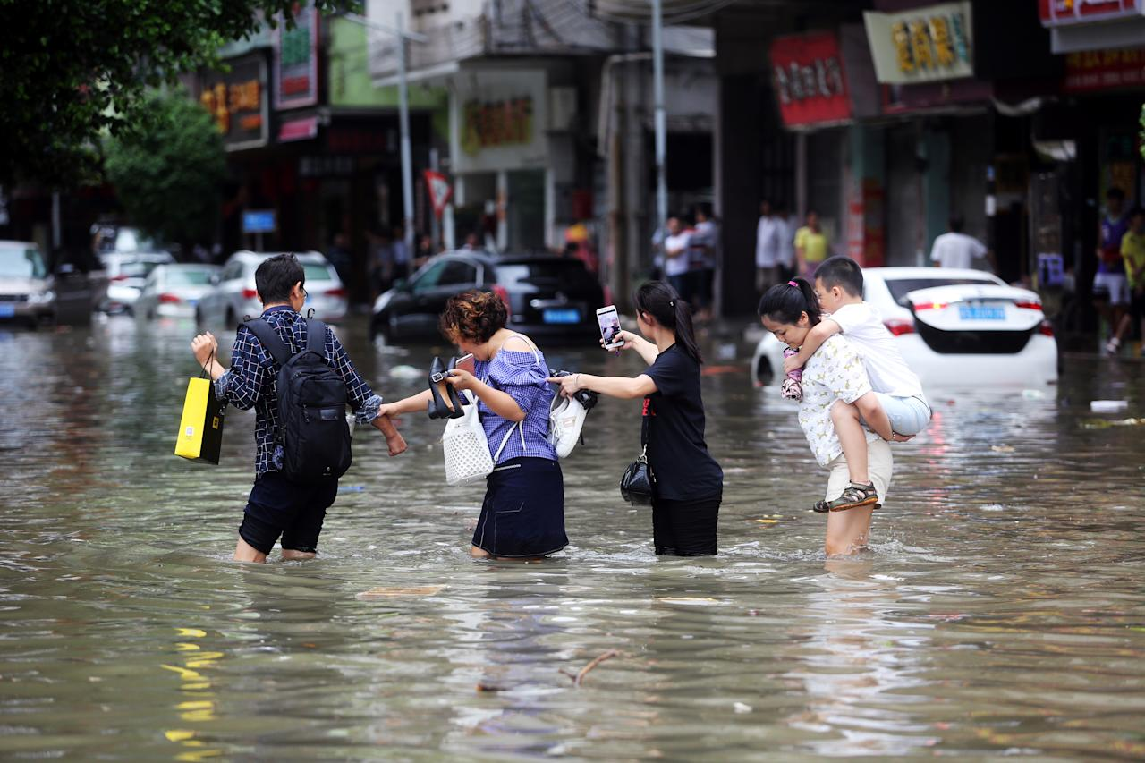 <p>People walk through a flooded street as Typhoon Hato hits Dongguan, Guangdong province, China, Aug. 23, 2017. (Photo: Stringer/Reuters) </p>