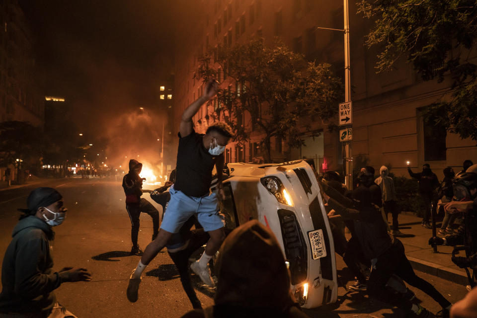 Demonstrators vandalize a car as they protest the death of George Floyd, May 31, 2020, near the White House in Washington, D.C. Floyd died after being restrained by Minneapolis police officers. The image was part of a series of photographs by The Associated Press that won the 2021 Pulitzer Prize for breaking news photography. (AP Photo/Evan Vucci)