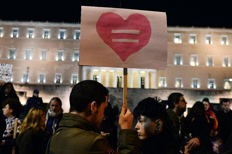 A man holds a sign during a demonstration outside the Greek parliament in Athens on December 22, 2015 (AFP Photo/Louisa Gouliamaki)