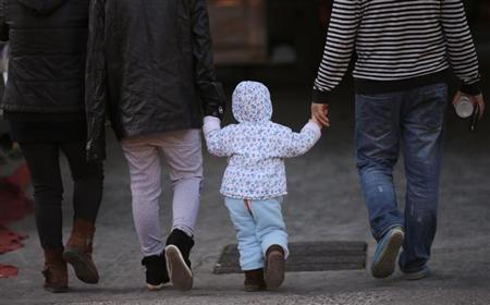 A girl holds the hands of her parents as they walk on a street in Beijing
