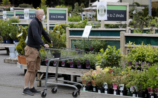 A customer shops near a social distancing sign at Osterley Garden Centre in London as the country is in lockdown to help stop the spread of coronavirus, Wednesday, May 13, 2020. Some of the coronavirus lockdown measures are being relaxed in England on Wednesday, with garden centres reopening but with extra measures such as social distancing. (AP Photo/Kirsty Wigglesworth)