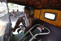 A COVID-19 patient breathes with the help of an oxygen mask as he waits inside an auto rickshaw to be attended to and admitted in a dedicated COVID-19 government hospital in Ahmedabad, India, Thursday, April 22, 2021. Indian authorities scrambled Saturday to get oxygen tanks to hospitals where COVID-19 patients were suffocating amid the world's worst coronavirus surge, as the government came under increasing criticism for what doctors said was its negligence in the face of a foreseeable public health disaster. (AP Photo/Ajit Solanki)