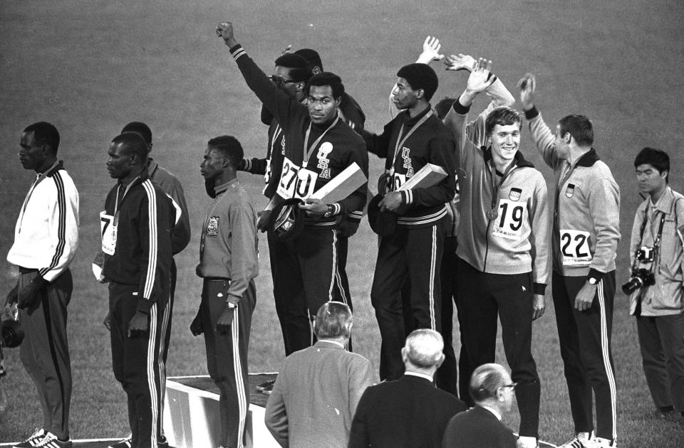 FILE - Lee Evans, a member of the United States 4X400-meter relay team, holds up a clenched fist after receiving his gold medal during medal presentations at the Mexico City Games in Mexico City, in this Oct. 21, 1968, file photo. Lee Evans, the record-setting sprinter who wore a black beret in a sign of protest at the 1968 Olympics, died Wednesday, May 19, 2021. He was 74. USA Track and Field confirmed Evans' death. The San Jose Mercury News reported that Evans' family had started a fundraiser with hopes of bringing him back to the U.S. from Nigeria, where he coached track, to receive medical care after he suffered a stroke last week. (AP Photo/FIle)