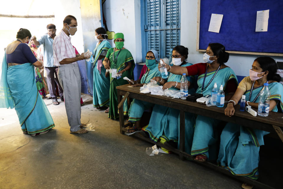 Volunteers offer gloves and sanitizers to voters at the entrance of a polling station during the fourth phase of West Bengal state elections in Kolkata , India, Saturday, April 10, 2021. (AP Photo/Bikas Das)