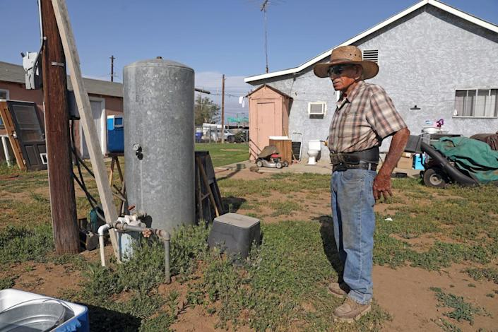 Rodolfo Romero near his 60-foot deep water well and pressure tank that provides water to the home.