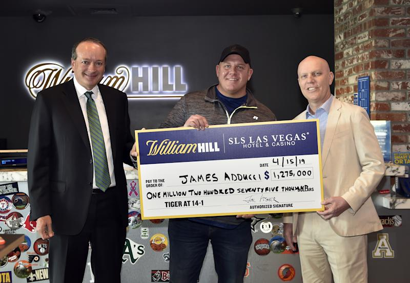 William Hill US CEO Joe Asher (left), James Adducci and SLS Las Vegas general manager Paul Hobson (right) stand with a ceremonial check of Adducci's winnings after cashing his winning ticket at the William Hill Sports Book at SLS Las Vegas Hotel on Monday.