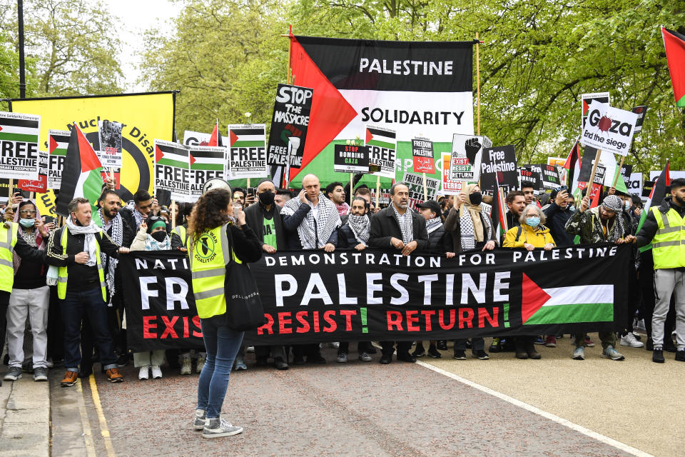 People hold placards and Palestinian flags as they march in solidarity with the Palestinian people amid the ongoing conflict with Israel, during a demonstration in London, Saturday, May 15, 2021.(AP Photo/Alberto Pezzali)