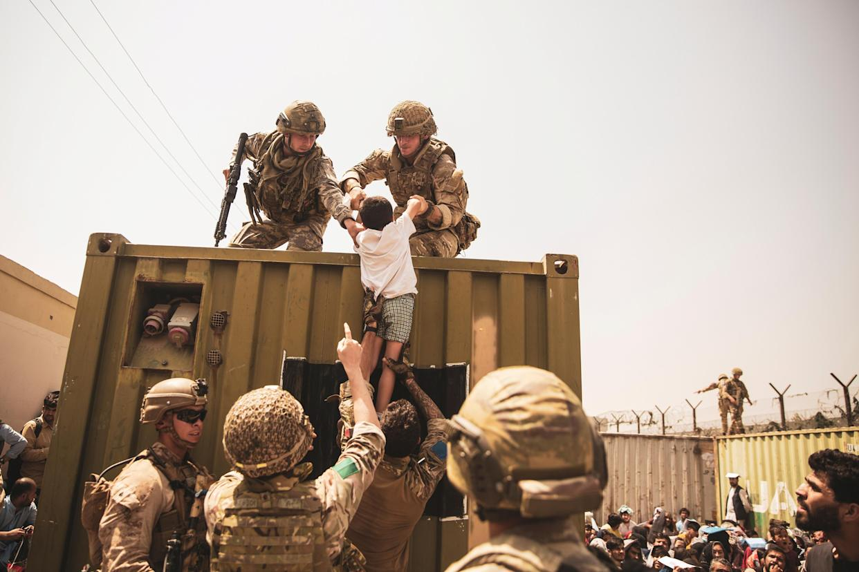 UK coalition forces, Turkish coalition forces, and U.S. Marines assist a child during an evacuation at Hamid Karzai International Airport, Kabul, Afghanistan, in this photo taken on August 20, 2021.  (Sgt. Victor Mancilla/U.S. Marine Corps/Handout via Reuters)