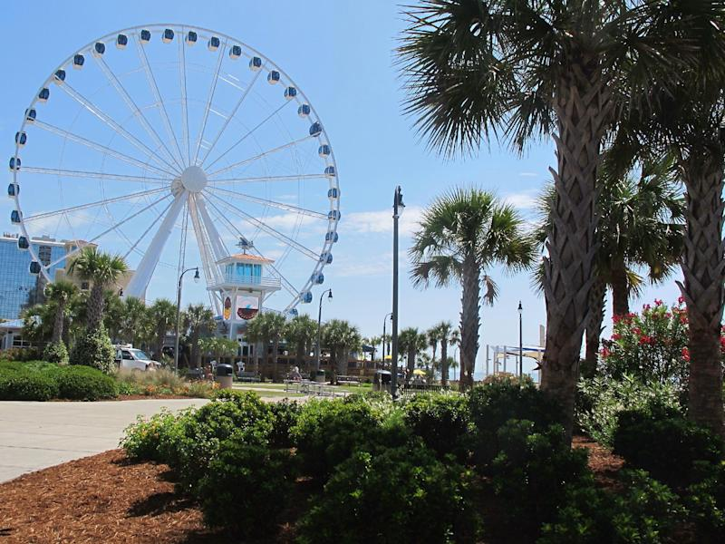 This May 22, 2013 photo shows Plyler Park, just off the boardwalk in Myrtle Beach, S.C. During the summer season, the park is the site of the Hot Summer Nights series of concerts and other events. In the background is the SkyWheel, the tallest Ferris wheel in the eastern United States. (AP Photo/Bruce Smith)
