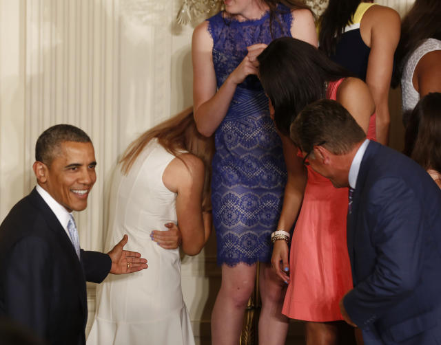 REFILE - CORRECTING SPELLING OF STEFANIE DOLSON'S FIRST NAME U.S. President Barack Obama walks over to help as Stefanie Dolson hides her head after slipping off the stage during a ceremony honoring the 2014 NCAA champion UConn Huskies men's and women's basketball teams in the East Room of the White House in Washington, June 9, 2014. REUTERS/Larry Downing (UNITED STATES - Tags: POLITICS SPORT BASKETBALL)