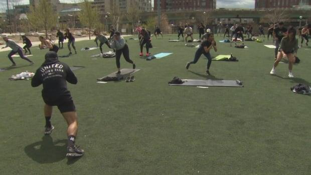 A workout group called United We Fight staged a demonstration on Sunday, with dozens partaking in a physically-distanced workout atCanoe Landing Park to protest the province's restrictions.  (CBC - image credit)