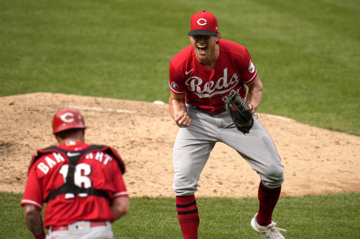 Cincinnati Reds pitcher Lucas Sims, right, and catcher Tucker Barnhart celebrate an 8-7 victory over the St. Louis Cardinals in a baseball game Sunday, June 6, 2021, in St. Louis. (AP Photo/Jeff Roberson)