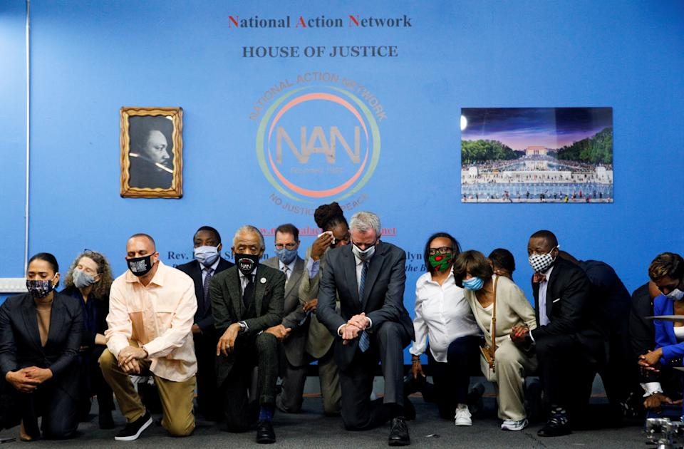 New York City Mayor Bill de Blasio and Rev. Al Sharpton kneel with community leaders for 9 minutes and 29 seconds on Tuesday, the first anniversary of the death of George Floyd. (Brendan McDermid/Reuters)