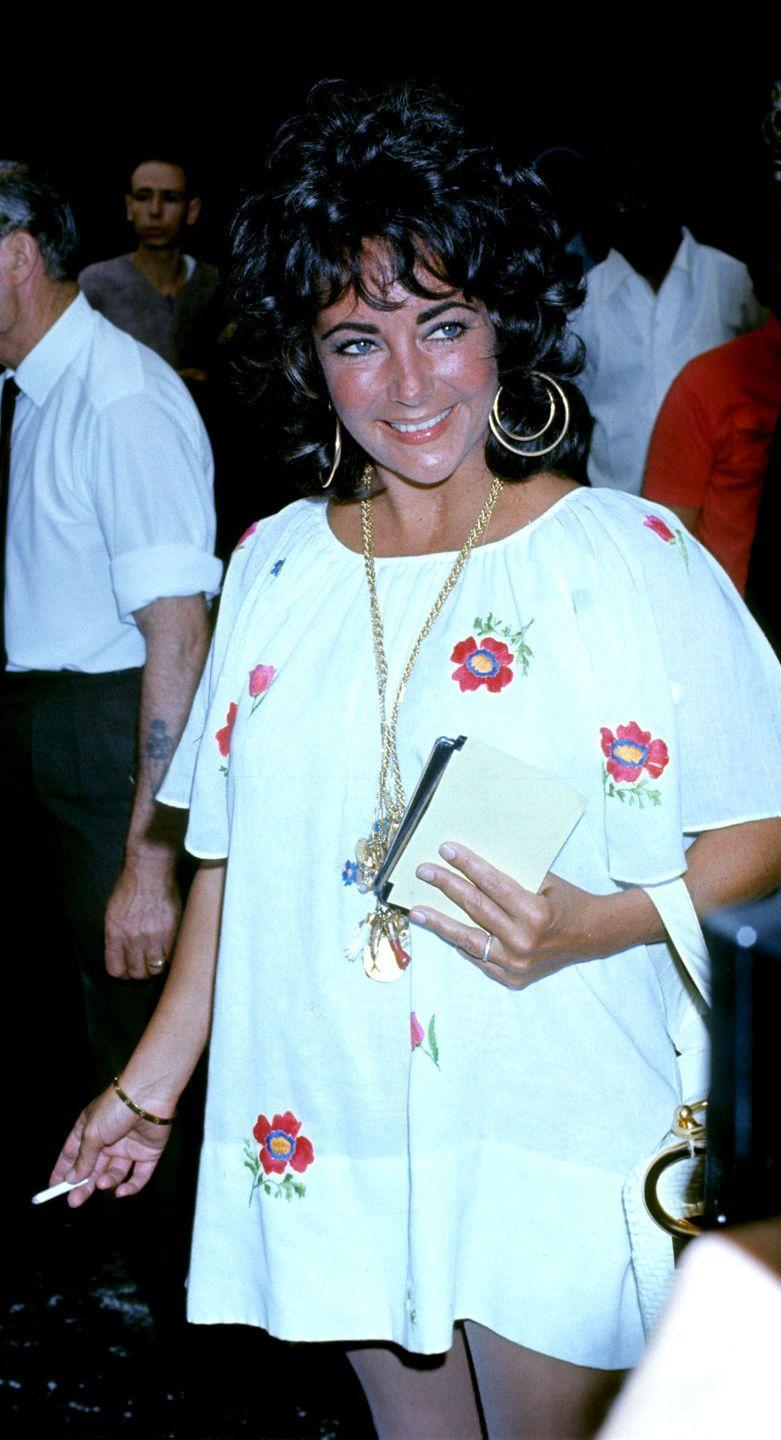 <p>Elizabeth is dialed into the '70s fashion cues as she leaves the airport in London, wearing a floral peasant dress and large gold hoops. </p>
